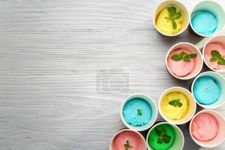 Photo pour Collection de crème glacée dans des tasses en papier sur fond en bois - image libre de droit