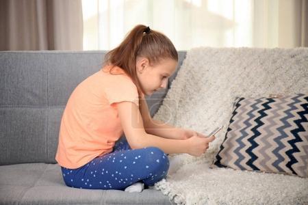 Cute schoolgirl with phone sitting on sofa