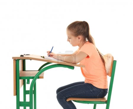 Schoolgirl sitting at desk on white background