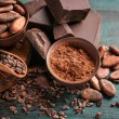 Bowls of cocoa beans and powder with broken chocol...