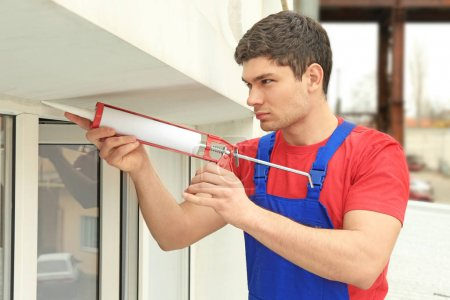 Photo for Young male worker sealing joints of office window - Royalty Free Image