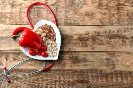 Photo for Healthy food in heart shaped plate on wooden background - Royalty Free Image