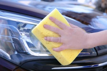 Female hand cleaning car