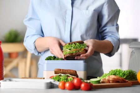 Photo for Mother packing meal for school lunch on table - Royalty Free Image