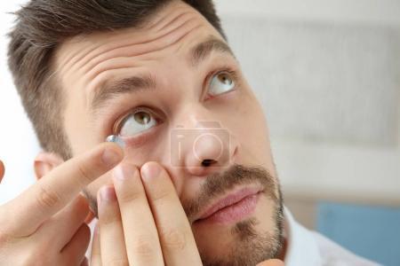 Young man putting contact lenses