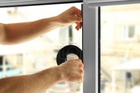 worker applying rubber strip onto window