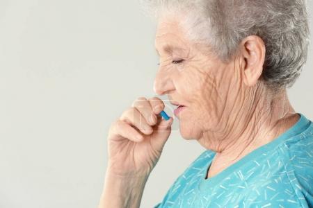 Elderly woman taking pill