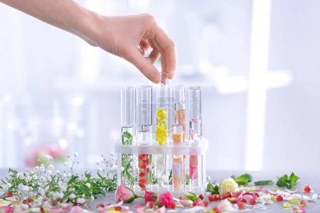 Photo for Woman mixing perfume samples on table - Royalty Free Image