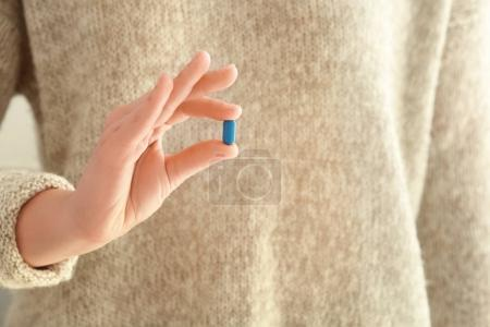 Young woman with pill