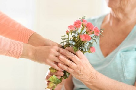 giving flowers to old woman