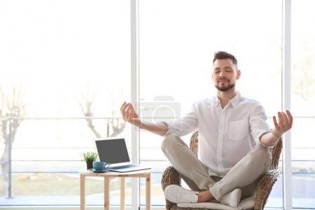 Happy young man meditating
