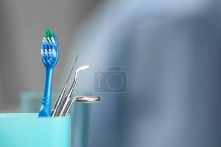 Cup with toothbrush and dental instruments