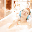Young attractive woman relaxing in bath with foam ...