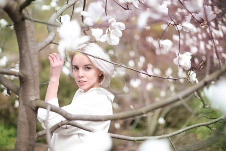 Young woman near blooming magnolia tree
