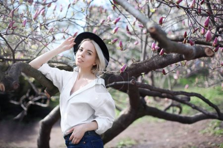 Young woman in hat near magnolia tree
