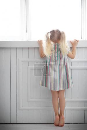 Photo pour Petite fille mignonne debout près de la fenêtre à la maison - image libre de droit