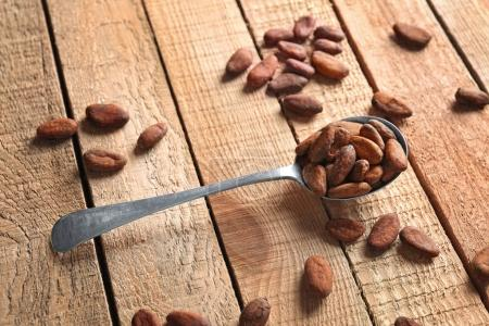 Spoon with aromatic cocoa beans on wooden table...