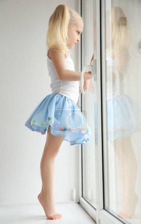 girl standing on windowsill
