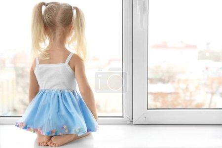 jeune fille assise sur le rebord de la fenêtre