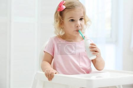 Cute girl drinking yogurt
