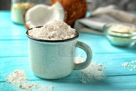 Cup with coconut flour on wooden background...
