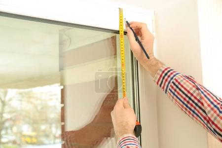 Male hands marking off window frame...