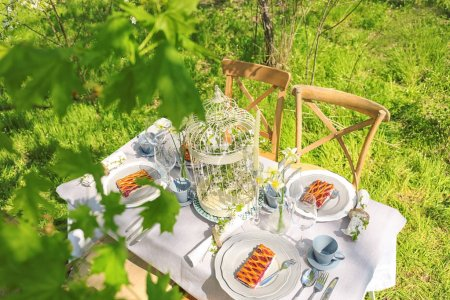 Table setting and cage with flowers