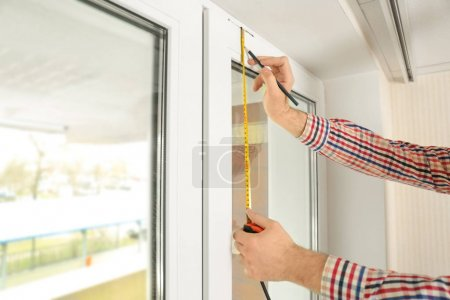 Man marking off window frame at home...