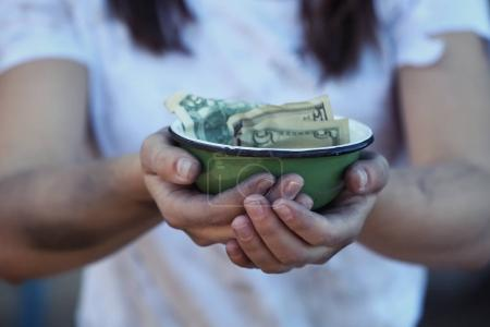 woman holding bowl with money
