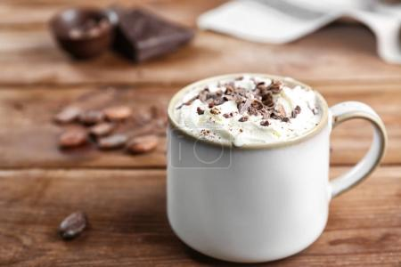 Cup of cocoa with whipped cream on wooden table...