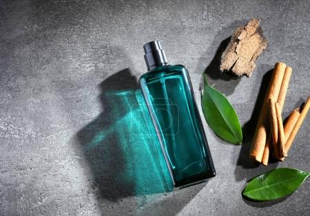 Photo for Botle of modern male perfume with pieces of cynamon and tree bark. - Royalty Free Image