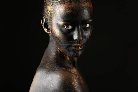 woman with dark paint and sparkles on body