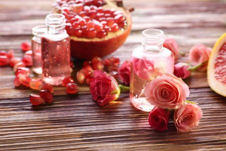 Photo for Perfume bottles, roses and pomegranate on wooden table - Royalty Free Image