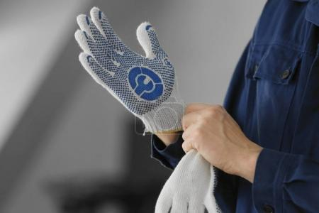 Hands of auto mechanic putting on gloves