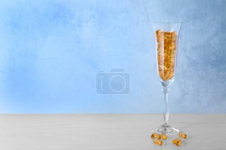 Wineglass with fish oil capsules
