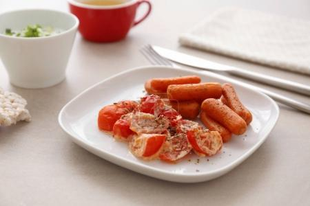 Plate with fried carrot and tomatoes