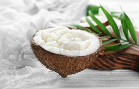 Photo pour Huile de coco fraîche en deux de noix sur table en bois - image libre de droit