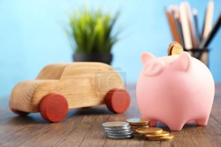 Piggy bank and wooden toy car