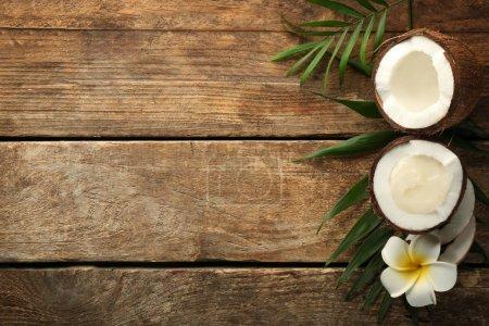 Photo pour Huile de noix de coco fraîche dans la moitié des noix sur fond en bois - image libre de droit