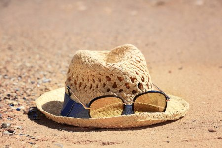 Hat and sunglasses on sand