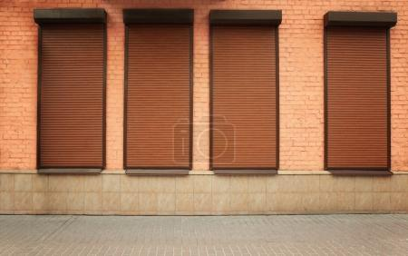 Windows with closed roller blinds in wall...