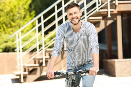 Handsome young man with bicycle outdoors on sunny ...