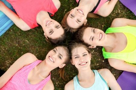 Photo pour Groupe de jeunes femmes allongées sur la pelouse après avoir pratiqué le yoga à l'extérieur - image libre de droit