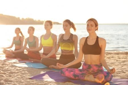Photo pour Groupe de jeunes femmes pratiquant le yoga en plein air - image libre de droit