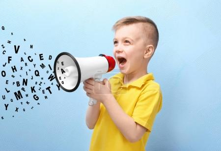 Photo for Little boy with megaphone and letters on blue background. Speech therapy concept - Royalty Free Image