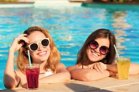 Two women with cocktails in pool