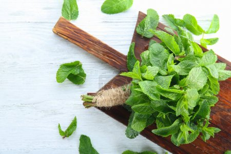 Bunch of fresh mint and wooden  board on table