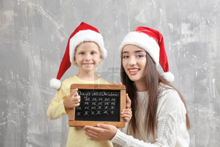 Young woman and cute little girl in Santa hats with chalkboard counting days until Christmas, on grunge background