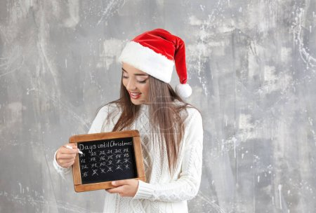 Young woman in Santa hat with chalkboard