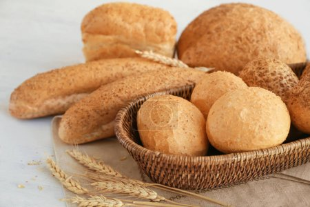 Wicker basket and delicious bread on wooden table